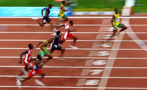 Usain Bolt (R) crosses the line.