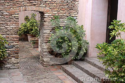 Interior of Alcazaba . Pots with plants , brick wall, arch, brick pavement
