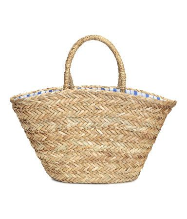Bag in thick, braided seagrass with imitation leather details, two short handles at top, two inner compartments, and striped cotton lining. Size 7 1/2 x 11 x 21 1/2 in.