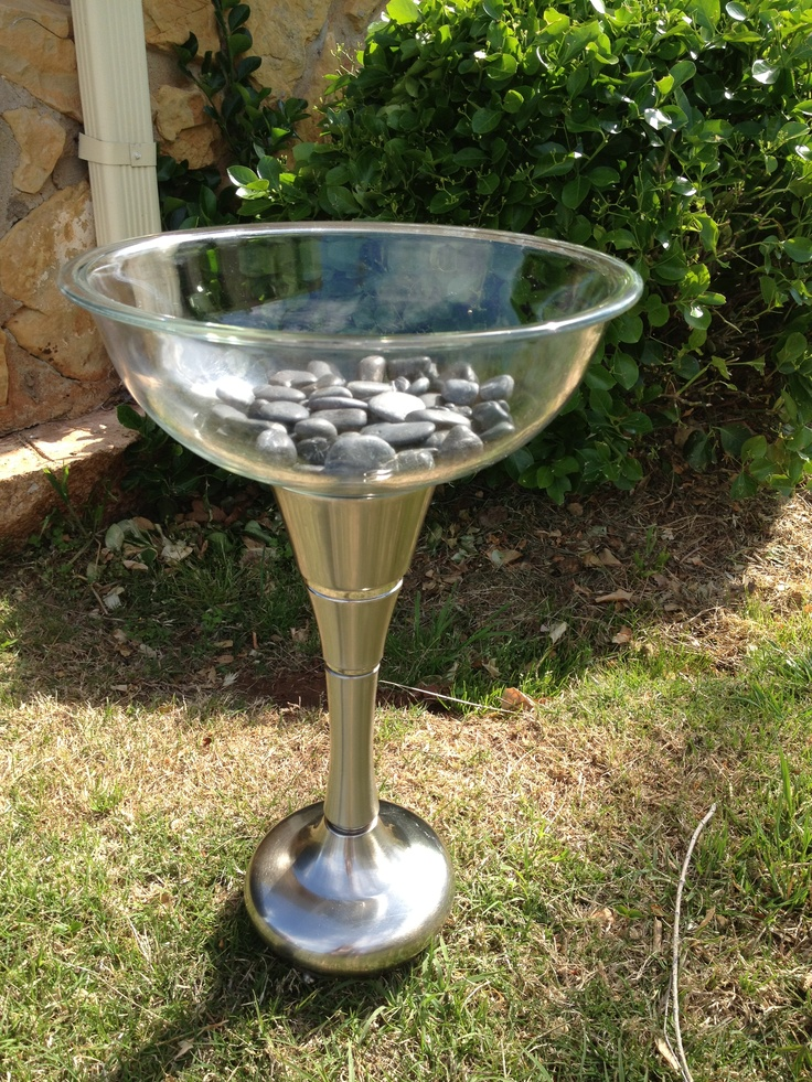 Contemporary bird bath I made with lamp base from thrift store along with a glass bowl from thrift store. Rocks to soften hard lines and make bowl not as deep. ( black river rock).