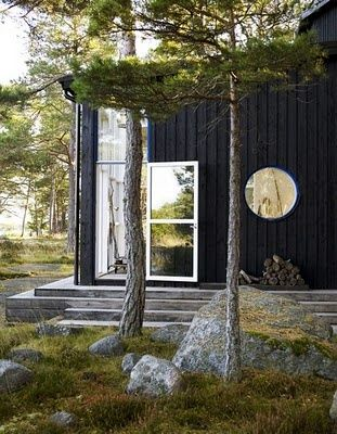 stenar, klippor i dagen, mossa, tallar, svart trähus, grånat trädäck följsamt med nivåer