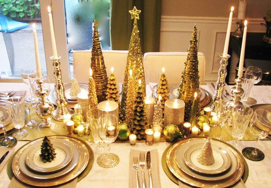 Christmas Table Ideas: Decorating with Silver and Gold - This table is a lovely blend of silver and gold candles, dinnerware and holiday decor. Using so many different styles and sizes of candles, makes this a lovely and interesting centerpiece. Notice the miniature trees at each place setting.