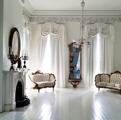 White sitting room with painted floors, tufted antique settees, carved mantle at the fireplace and tall windows... A room for dancing