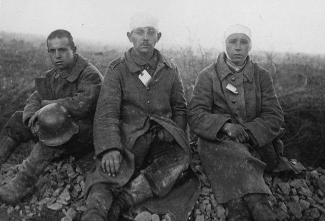 Three young-looking German prisoners of war. Their clothes are caked in mud and are a mishmash of styles. The soldier on the left still has his helmet, but the others have bandages wrapped round their heads