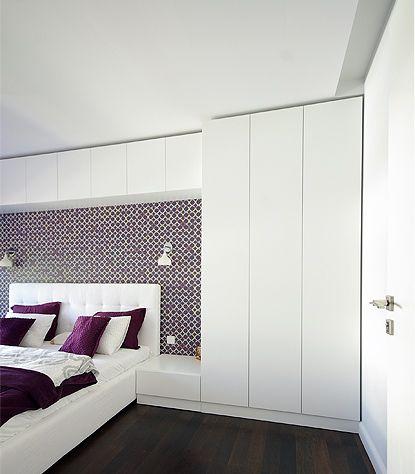 Zabudowa w sypialni w postaci białych szaf i pawlaczy bez uchwytów, otwieranych…