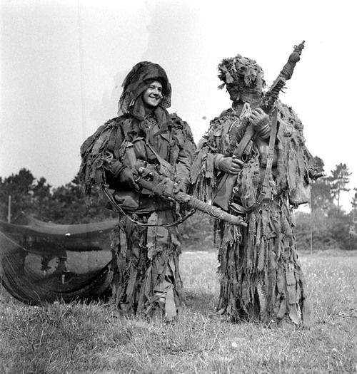 """Two snipers of the 1st Canadian Parachute Battalion wear their """"ghillie"""" suits during an inspection by King George VI, Queen Elizabeth and Princess Elizabeth. England, 17 May 1944."""