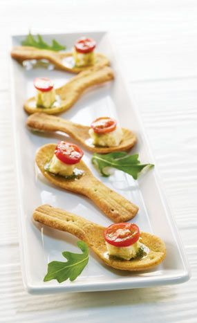Leek cheesecake (!?) with arugula pesto, caramelized onions, and a sweet grape tomato served in a pesto cracker spoon, by Puff 'n Stuff Catering in Orlando & Tampa, Florida.