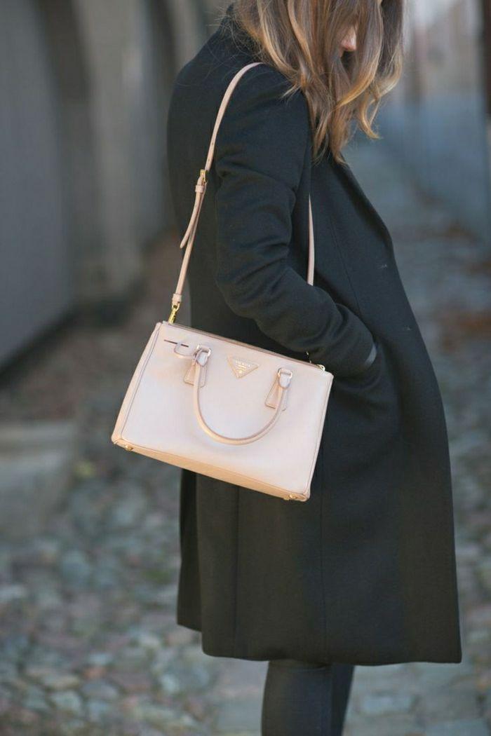 Designer Tasch in Pastellfarbe auf schwarzem Mantel