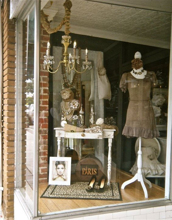 """Simple window: One showpiece people will give your WOM about (""""the shop with the chandelier""""), one dress form (easier than a mannequin) and one mood-setting piece of furniture you use as a riser. Notice, too, the area rug """"grounding all together, placed on an angle leading customers to door."""