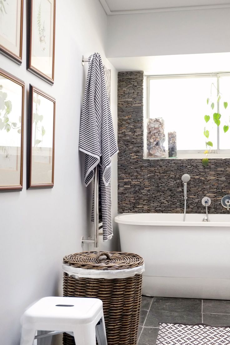 They renovated the entire bathroom and added the stonework mosaic to match the stone flooring. They bought the Victoria and Albert tub because it fitted the space perfectly and for its beautiful shape. The towels are from Country Road, wicker basket from Mr Price Home and the stool from Chair Crazy. The fern artworks were done by Megan's mother, botanical artist Sylvia Beath.