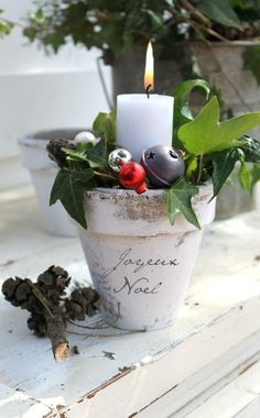 Christmas centrepiece. Whitewashed terracotta pot, simple candle, greenery, bells, berries.