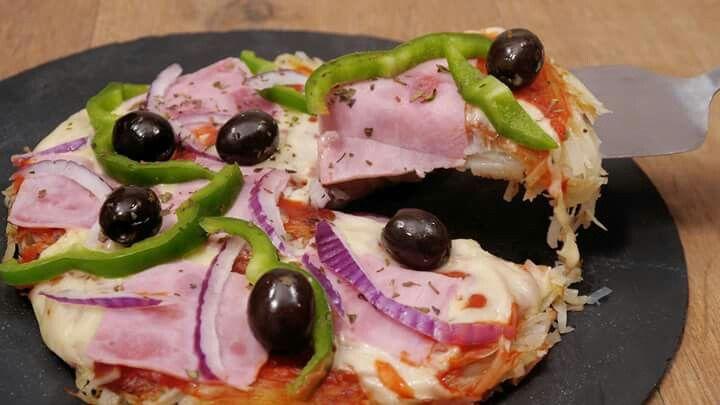 (3 pers):500g de papas-Salsa de tomate-Queso-Jamón- Pimentón verde-Cebolla- ceitunas - Orégano - Sal.Pela las papas y córtalas en tiras.Calienta aceite en una sartén, y cocina las papas formando una especie de tortilla entre 15  minutos por lado o hasta que estén tiernas. Rellena la pizza con salsa de tomate, queso, jamón, pimentón verde,aceitunas, cebolla o tus agregados preferidos. Alíñala con sal y orégano.Cubre la pizza con una tapa y cocínala a fuego bajo durante 15 min/queso derretido