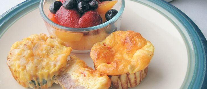 """WP 2 MOTHER: Breakfast Sausage & Egg MUFFINS served with fruit; Fruity BRAN Muffins with cheese. (An easy Mother's Day breakfast. Or make a large batch to tuck into a busy mom's freezer. They can be made ahead and reheated for a quick breakfast or work lunch.) """"Honour young mothers with breakfast treat."""" Recipe. ~ The Western Producer"""