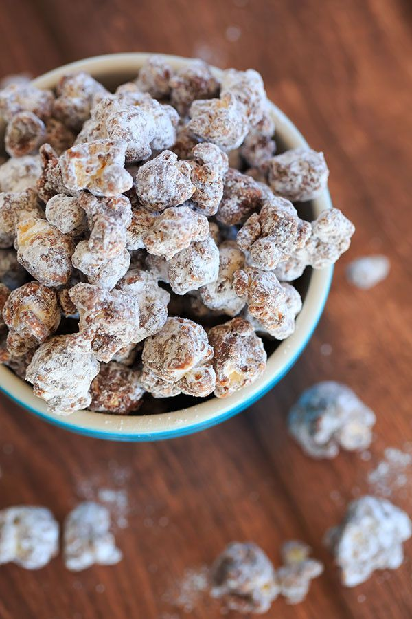 "This popcorn version of the enormously popular muddy buddies (or ""puppy chow"") is chocolate and peanut butter-covered popcorn tossed in powdered sugar. 