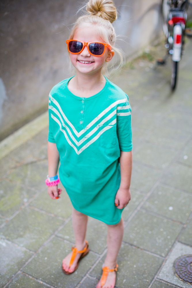 Little girl outfit: turquoise dress with white chevron design, orange sandals and glasses.