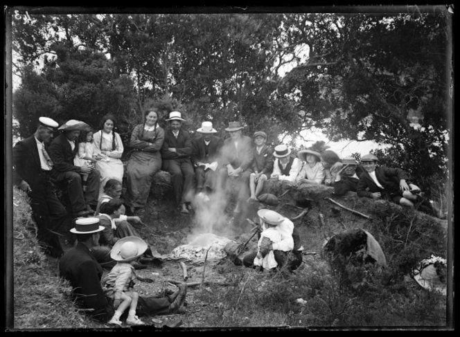 Group of men, women, and children, around a hangi 1913