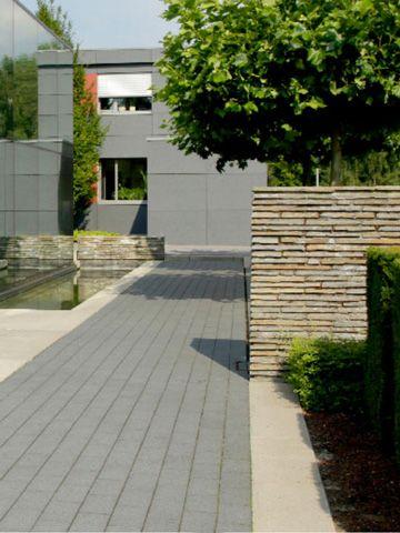 Die Natursteinmauern Im Haupteingangsbereich Bilden Einen Starken Kontrast  Zu Der Glatten Materialität Seiner Umgebung. Wasserreflexionen