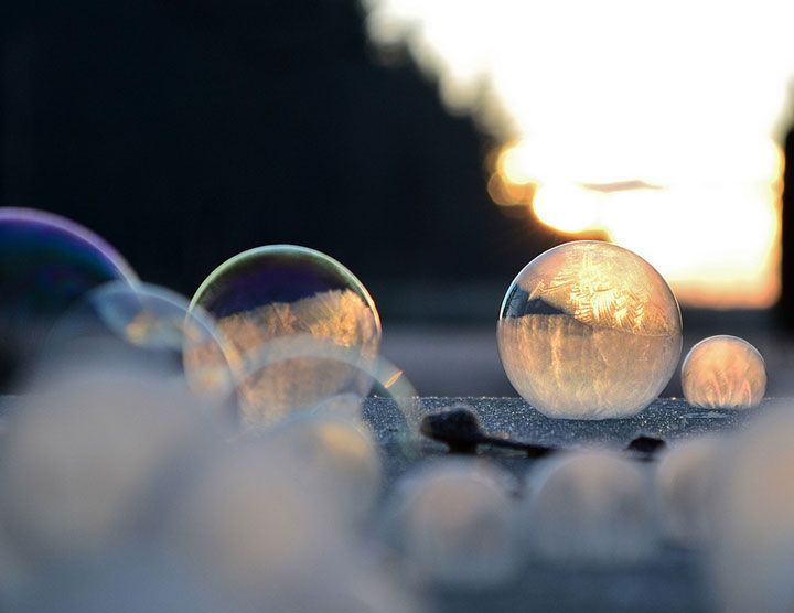 Un petit garçon souffle des bulles de savon qui se cristallisent dans le froid hivernal
