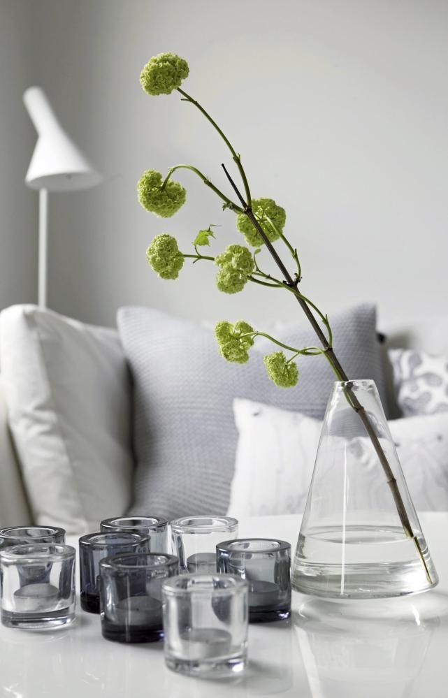 En enkel kvist med grønne blader har fått sin plass i en vase med vann, og fungerer som en frisk fargeklatt i det lyse rommet som ellers er preget av lyse farger.