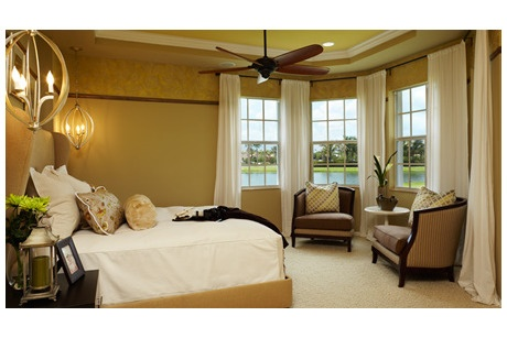A wall of windows offers a water view from this master bedroom. The Pesaro by Toll Brothers. Jupiter Country Club - Carriage Homes. Jupiter, FL.