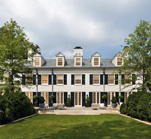 GARDEN FACADE OF BOXWOOD, A HISTORIC HOME BUILT IN 1914 BY ARCHITECT CHARLES PLATT, LOCATED IN THE EXCLUSIVE BELLE MEADE SECTION OF NASHVILLE. THE WHITE BRICK HOUSE FEATURES BLACK SHUTTERS, AN EXPANSIVE REAR TERRACE AND GORGEOUS GARDENS DESIGNED BY PAGE DUKE LANDSCAPE ARCHITECTS.