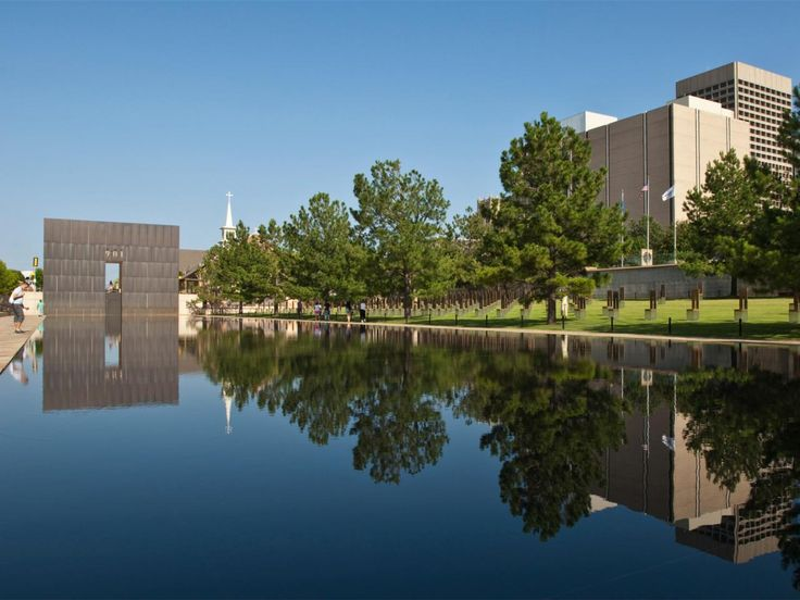 The Oklahoma City National Memorial honors all who were affected by the Oklahoma City bombing in 1995. The memorial includes a reflecting pool, field of empty chairs, survivors' wall and survivor tree. The eastern gate, seen here, represents the last minute of peace before the bombing.
