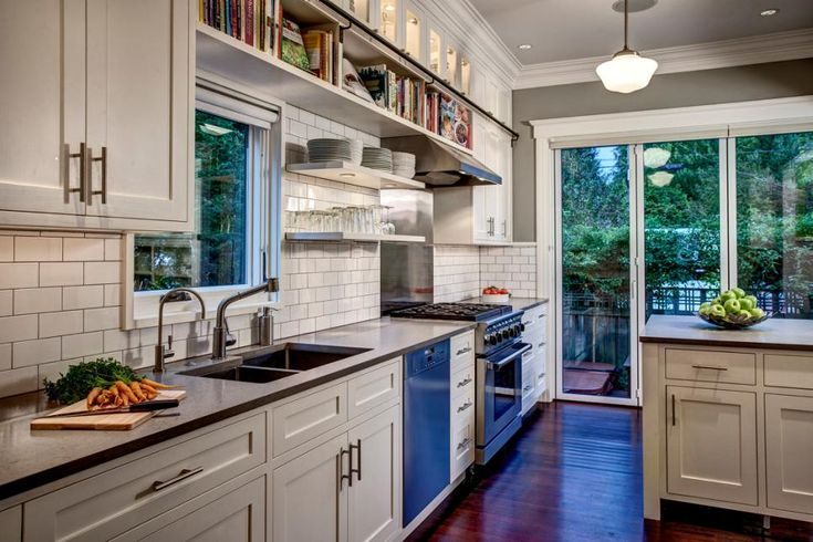 Open shelves keep cookbooks and everyday tableware handy but off the countertops in this transitional kitchen. Roller shades on the glass doors and window allow for natural lighting or privacy. A white subway-tile backsplash with gray grout complements the room's white and gray color scheme.