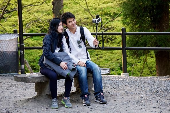 A happy looking couple using a selfie stick to take a selfie while sitting in on bench in a lush green park in Kyoto Japan Spring 2014