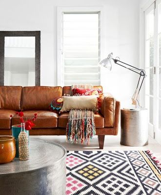 Caramel sofa with colourful Moroccan pillows, textured multi-colour throw and ethnic rug.