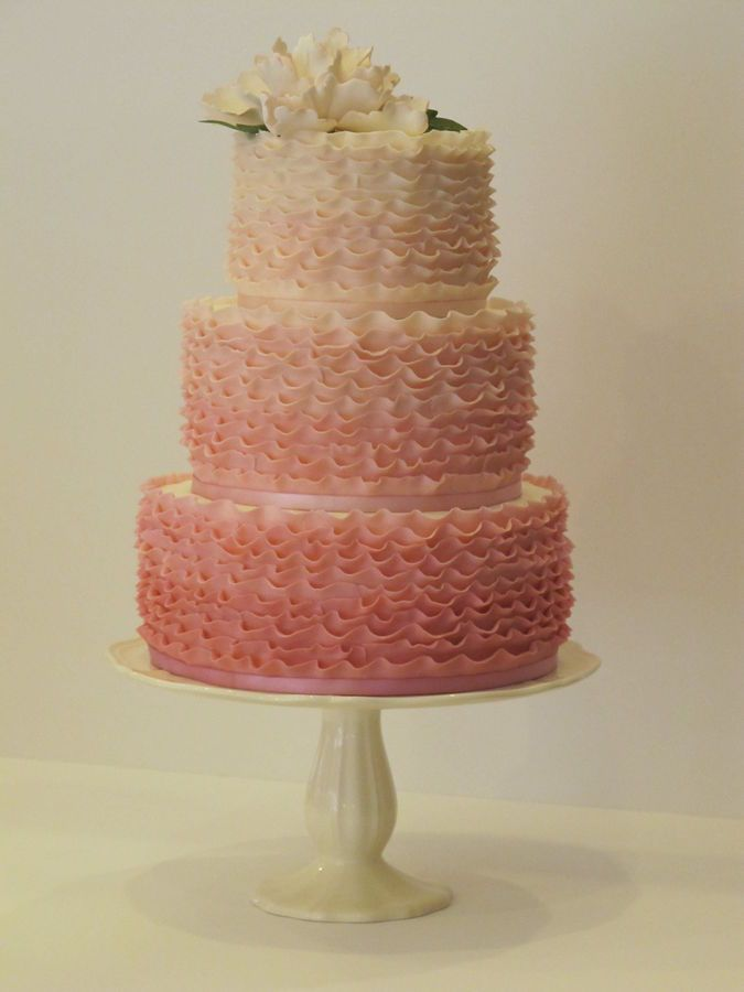 6', 8', and 10' Vanilla Bean Cake with raspberry filling, lemon curd filling and frosted in IMBC.  Covered in ombre white chocolate ruffles.  A handmade sugar open peony on top.