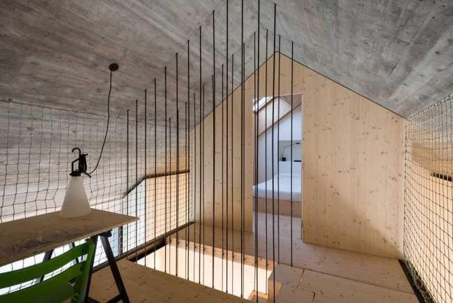 Pod strechou je lávka, ktorá spája obe spálne a slúži aj ako detská izba na hranie. Z bokov je uzavretá lanovou sieťou kvôli bezpečnosti.
