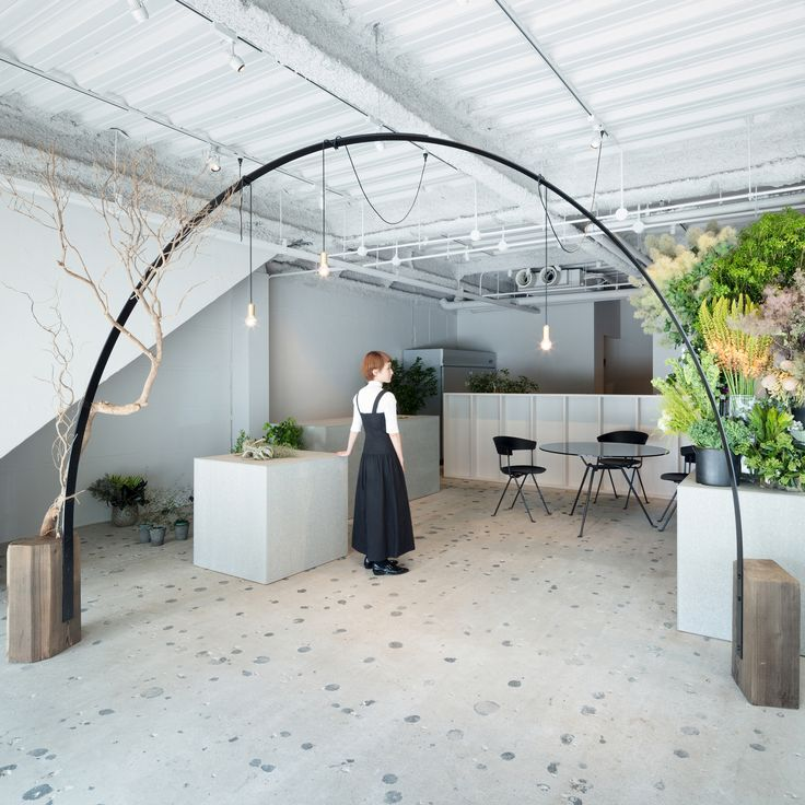 A tree branch and pendant lights wrap around the black metal arch that interior design studio Sides Core has placed inside this Japanese florist.