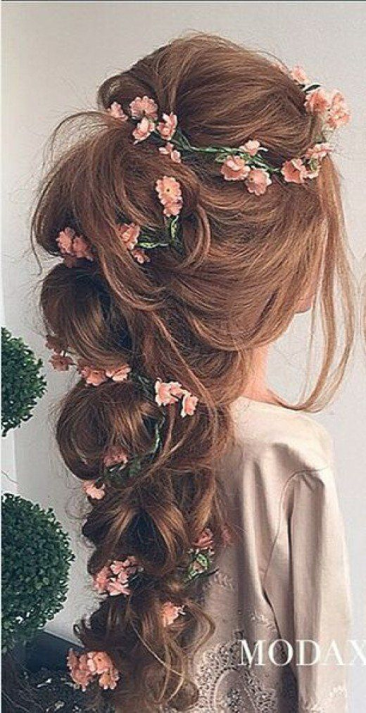 Most romantic bridal hairdo with thick loose braid and artfuly planted pink tiny flowers and green wines.
