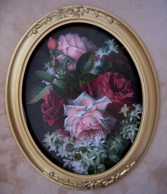 This gold toned composite frame holds one of our reproduction prints that showcases a bouquet of pink hued roses and white clematis blooms on a dark background. The print is a study by the Victorian watercolorist Paul de Longpre. The roses are just beautiful, a bit pinker than shown, and lovely against the dark background. The frame has a raised floral ornamentation at each end. (Please disregard any glass glare reflection lines due to the bubble glass, and do see the second closeup photo…