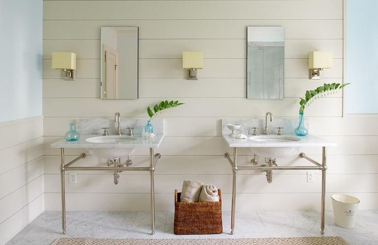 Beautiful cream and blue bathroom is illuminated by nickel sconces with cream shades mounted to a cream shiplap backsplash flanking inset frameless medicine cabinets fixed above his and hers nickel and marble washstands.