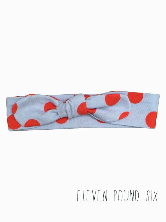 Red spotty  bow knot topknot headband on a pale blue grey background