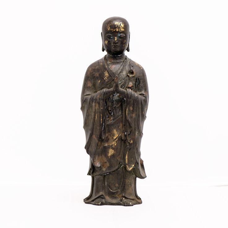 """Buddha-Figur Ananda aus Bronze  Diese Buddha-Figur ist aus Bronze gefertigt, die stellenweise golden schimmert. Sie stellt Ananda, den Cousin Buddhas dar. Sein Name bedeutet """"Abwesenheit von Unglück"""". Ananda gilt als Lieblingsjünger Buddhas und als Bewahrer seiner Lehre. Die Figur ist stehend dargestellt. Sie strahlt Ruhe und Harmonie aus. Das Gewand ist liebevoll ausgearbeitet und zeigt einen weichen Faltenwurf. Die Figur ist in Handarbeit gefertigt."""