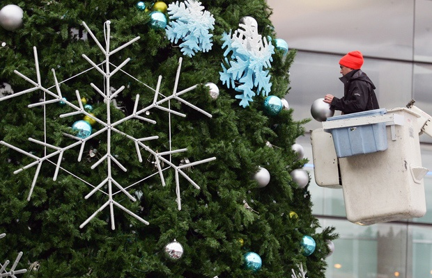 Michael Fisher places a giant globe on the City of Surrey Christmas Tree, which is being set up and decorated in the plaza in front of Central City. The city's tree lighting ceremony is set for this Saturday, Nov. 24 with plenty of free family events planned.