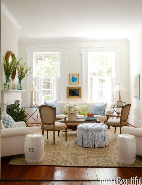 """""""No fuss"""" was Lynn Morgan's mantra when she decorated her Savannah row house: """"I wanted it simple, clean-lined, and inviting, with a little bit of glamour and a lot of comfort."""" An ottoman in Zig Zag by Alan Campbell lends modern oomph between a pair of Louis XV style bergères. To highlight the architectural details, she painted moldings in high-gloss white. A David Hockney lithograph hangs above an antique mercury glass mirror. Garden stools from Emissary."""