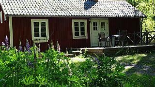 Tolles rotes Ferienhaus am Fluss inmitten vieler Seen und Wald