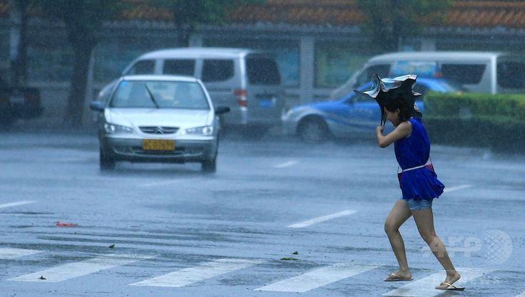 中国南部・海南(Hainan)省で、超大型の台風9号(アジア名:ラマスーン、Rammasun)の暴風雨のなかを歩く女性(2014年7月18日撮影)。(c)AFP ▼21Jul2014AFP 超大型の台風9号、中国南部でも猛威 死者17人 http://www.afpbb.com/articles/-/3021050 #Guangxi #Typhoon_Rammasun