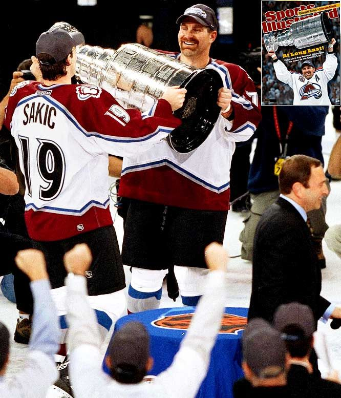 joe sakic hands the cup to ray bourque to hoist the Cup for the first time