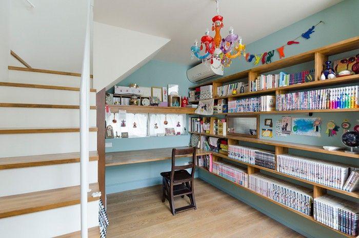 「自分の好きなようにつくれてとても気に入っている」という奥さんの作業スペース。以前マンガを描かれていたので、棚にはマンガの本がずらりと並ぶ。机の上部には、仕事でつくられた刺繍によるアクセサリーが並ぶ。