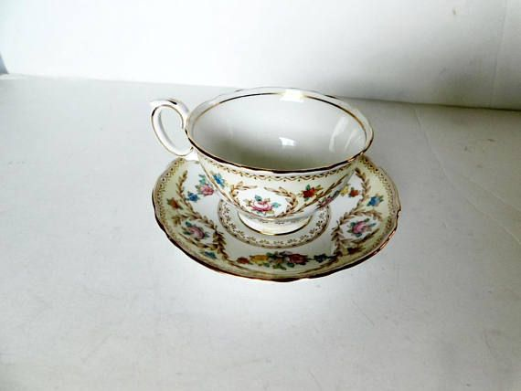 "Cup and saucer in pattern F15744, a multicolored floral and laurels design, gold accenting  The cup is 2 1/2"" (6.4 cm) high x 3 11/16"" (9.4 cm) at the brim and the saucer is 5 1/2"" (14 cm) in diameter  This set is in very good condition  Made of fine bone china from England by Crown Staffordshire    These items have no nicks, chips, cracks, or signs of repair 