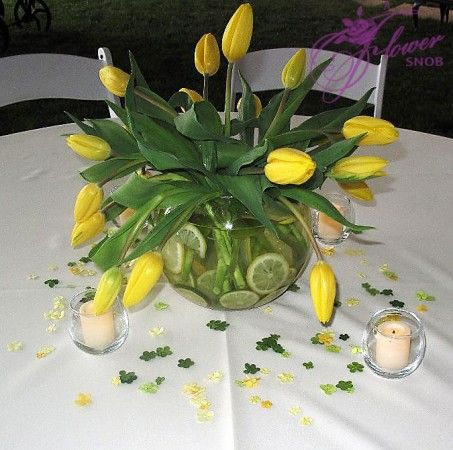 Bubble bowl arrangement with yellow tulips. Inside the bowl are slices of lemon and limes.