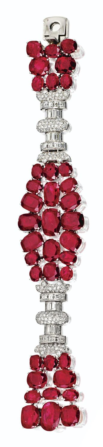 RUBY AND DIAMOND BRACELET, FRENCH, CIRCA 1930 The stylized strap set with 38 cushion-shaped and oval rubies weighing approximately 70.00 carats and with numerous round, single-cut, square-cut and baguette diamonds weighing approximately 5.60 carats, mounted in platinum