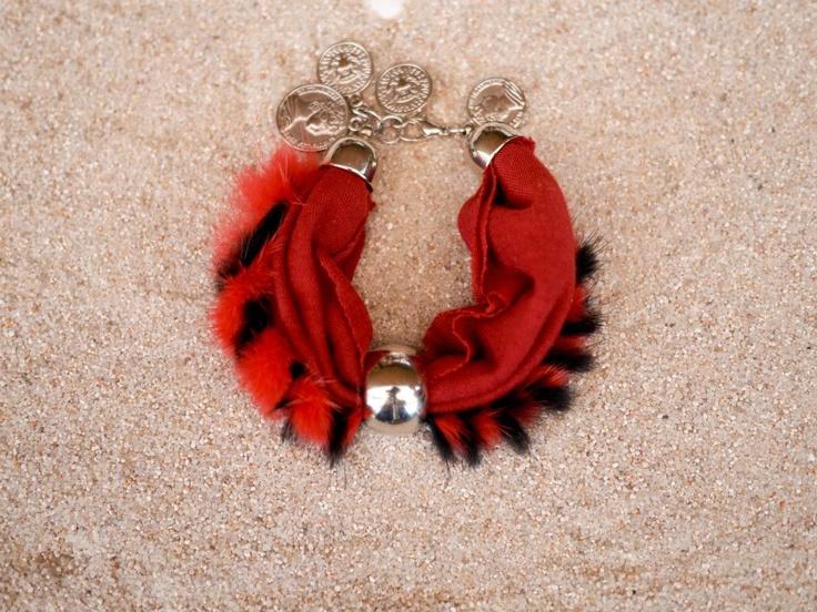 Pulsera de dos tela granate y otra de pelo suave rojo y negro. Varios adornos de monedas en el cierre y una bola grande plateada que se puede mover a lo largo de la pulsera.