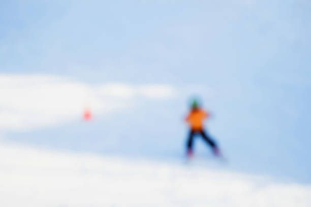 blur image of little skier learning downhill alpine skiing concepts