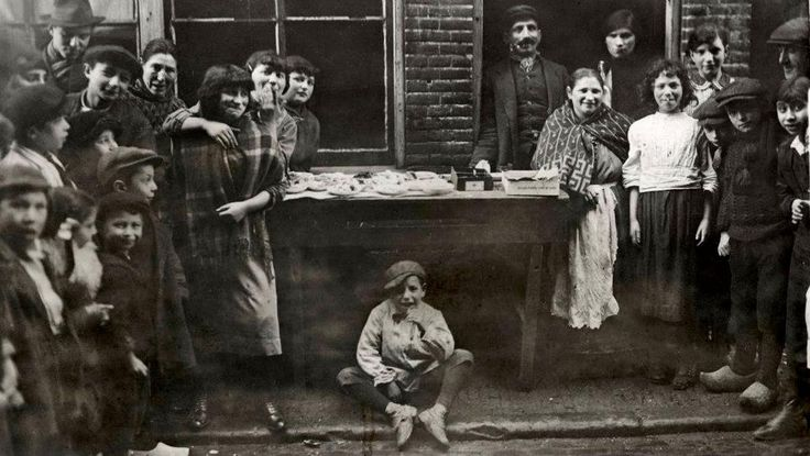 1916 Jodenbuurt.  Aan de snoep tafel. Volwassenen en kinderen kunnen voor een halve cent een stukje gekleurd suikergoed kopen. Een lichtpuntje in hun grauwe bestaan