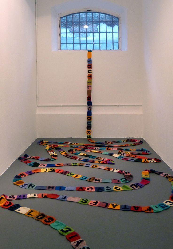 Paz Carvajal | El lento paso del tiempo, Intervención en celda, 32 m de texto tejido, Fragmento del poema Heráclito de Jorge Luis Borges
